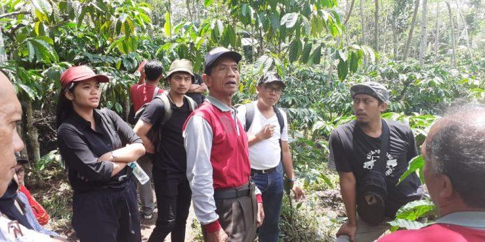 Salah satu petani kopi (berkaus merah) menerangkan ke peserta